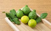 Постер, плакат: Green Kaffir Lime With Lemon Lime On Wooden Tray