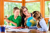 Постер, плакат: Homeschooling mother teaching kids private lessons in geography