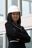 foto of hard_hat  - female asian engineer with arms folded wearing white hard hat - JPG