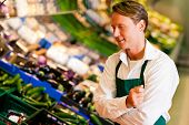 stock photo of grocery store  - Shop assistant in a supermarket at the vegetable shelf inspecting the stuff for sale - JPG