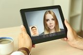 Young couple talking to each other via online video chat. poster