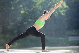 stock photo of virabhadrasana  - Beautiful sporty fit blond young woman in green sportswear working out outdoors standing in variation of Warrior I posture  - JPG