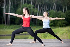 picture of virabhadrasana  - Two fit young beautiful women working out outdoors in park on summer day wearing sportswear red and blue tank tops doing Warrior II posture  - JPG