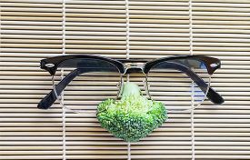 stock photo of cruciferous  - face of fresh broccoli with glasses on pattern bamboo for background - JPG