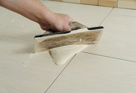stock photo of grout  - The hand of man holding a rubber float and filling joints with grout - JPG