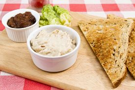 picture of canard  - a pot of creamy salmon pate on a wooden board with pickle and triangles of toast - JPG