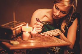 picture of vedic  - Woman drawing f henna menhdi ornament on her hand  - JPG