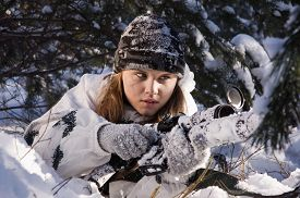 foto of sniper  - Sniper girl in white camouflage aiming with rifle at winter forest - JPG