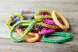 pic of rubber band  - Colorful rubber band bracelets on grey wooden background