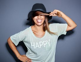 picture of sticking out tongue  - lively happe young woman in a trendy hat sticking out her tongue with a laughing smile as she holds a strand of her hair across her eyes - JPG