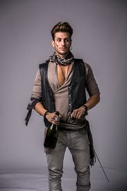 stock photo of pirates  - Good Looking Young Man in Pirate Fashion Outfit on Gray Background. Captured in Studio.