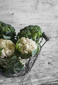 pic of cruciferous  - fresh cauliflower and broccoli in a vintage metal basket on a light wooden surface - JPG
