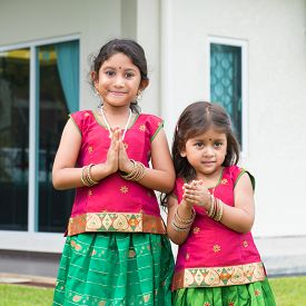picture of house representatives  - Cute Indian girls dressed in sari with folded hands representing traditional Indian greeting - JPG