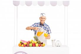 stock photo of jerks  - Senior soda jerk pouring orange juice into a glass and looking at the camera isolated on white background - JPG