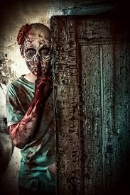 stock photo of doomsday  - Horrible scary zombie man on the ruins of an old house - JPG