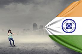 image of indian flag  - Portrait of young woman with casual clothes smiling at the camera while pulling an indian flag outdoors - JPG