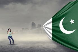 image of pakistani flag  - Portrait of young pakistani woman with casual clothes pulling a big flag of pakistan - JPG