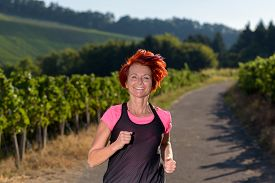 picture of vivacious  - Pretty vivacious redhead woman out jogging through country vineyards in evening light smiling as she approaches the camera - JPG