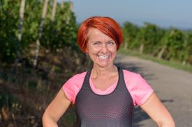 stock photo of vivacious  - Healthy vivacious pretty redhead woman out for her evening jog standing on a road between vineyards smiling at the camera with a lovely charismatic smile - JPG
