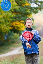foto of frisbee  - Artful guy with two Frisbee on the background of autumn yellow forest - JPG