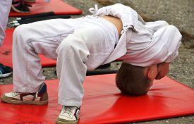 foto of judo  - young judo athlete makes a bridge in a white kimono with a red carpet  - JPG