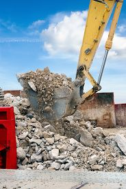 stock photo of power-shovel  - digger shovel while moving debris in the town - JPG