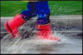 foto of rainy day  - Child in Red rain boots running through a puddle on a rainy day - JPG