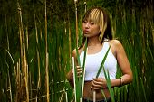 stock photo of braless  - An attractive female in a white tank top holds onto some grass - JPG