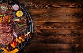 Top view of fresh meat and vegetable on grill placed on wooden floor. Barbecue, grill and food conce poster