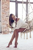 Young woman chilling at home in comfortable hanging chair in front of big window. Girl relaxing in s poster