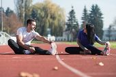 Couple Runner Stretching Leg In A City Park poster