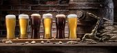 Glasses of beer and ale barrel on the wooden table. Craft brewery. poster