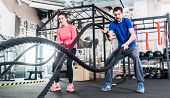 Woman and man in gym functional training with battle rope exercising poster