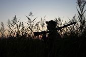 picture of duck-hunting  - Silhouette of the hunter on a background of a morning dawn - JPG
