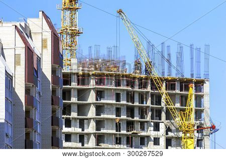 poster of Finished Apartment Building And A New High-rise Building Construction Site With Yellow Cranes Agains