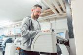 Man preparing large format printer for a banner print job on vinyl poster
