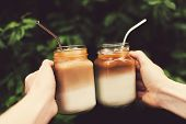 Two Glass Jars Of Ice Coffee Metal Straws In Woman And Man Hands. Clink Cups Of Coffee.  Outdoor Sho poster