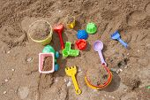 Bright Plastic Childrens Toys In The Sand. Concept Of Beach Recreation For Children. Kids Summer Gam poster