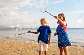 Kids Blow Bubble At Beach. Child With Bubbles poster