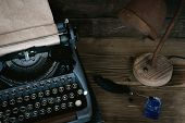 Typewriter, Blank Book Page And A Quill Pen With A Inkwell On An Author Desk Table Background. poster