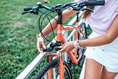 Close-up Girl Hand Lock With Digital Cipher. Woman Summer Stands Bicycle Locking Bicycle With Cable. poster