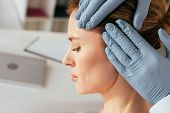 Cropped View Of Dermatologist In Latex Gloves Examining Hair Of Attractive Patient In Clinic poster