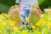 Child Lying On Green Grass. Kid Having Fun Outdoors In Spring Park. Child Feet With Painting Smiles  poster