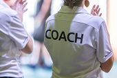 Female Coaches In White Coach Shirt At An Indoor Sport Game poster