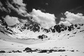 Plateau In High Snowy Mountains With Frozen Lake Covered Snow And Cloudy Sky At Sunny Spring Day. Tu poster