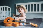A Portrait Of Very Cute 1 Year Old Baby With Musician Looks Wearing Hat And Holding Small Guitar Or  poster