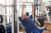 Lying Senior Man Lifting Weight At Gym. Mature Man Lifting Heavy Weight In Gym. Weight Workout. poster