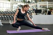 Young Fit Woman Stretching Leg At Gym. Beautiful Slim Woman Stretching On Yoga Mat At Fitness Center poster