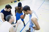stock photo of pep talk  - High angle view of coach talking to basketball team - JPG