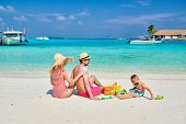Family on beach, young couple with three year old boy. Woman applying sun screen protection lotion o poster